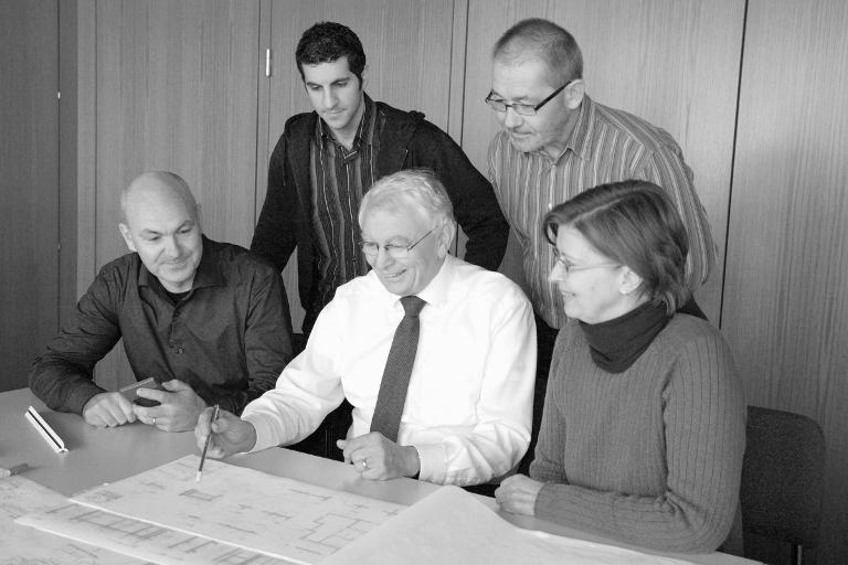 Dr. Ketterer und Herr Rödel mit einer Gruppe von Personen beim inspizieren von Plänen